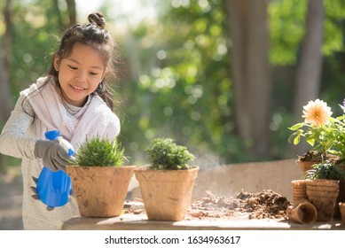 adorable 8 years old asian little girl is watering plant in pots in garden outside house, child education of nature. caring for a new life. earth day holiday concept. world environment day. ecology.