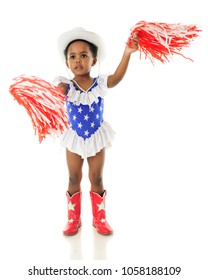 An adorable African American 2 year old in a western red, white and blue outfit shaking her pom-poms for the USA.  On a white background.