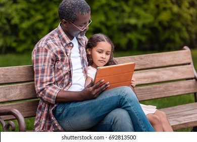 adorable african american girl and her grandfather using digital tablet sitting on bench in park