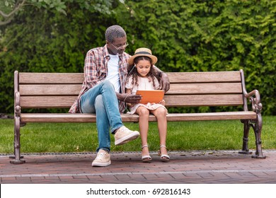 adorable african american grandchild and her grandfather listening music on digital tablet while sitting on bench in park