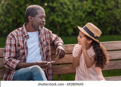 adorable african american granddaughter talking with her grandfather sitting on bench in park