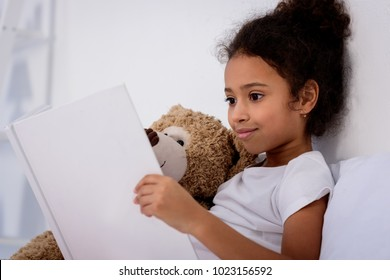 adorable african american kid reading book and hugging teddy bear at home