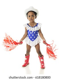 An adorable African American patriot shaking pom-poms while dressed in a star studded, red, white and blue western outfit.  On a white background.