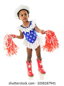 An adorable African American toddlerholding red and white pom poms and dressed for an American patriotic holiday.  On a white background.