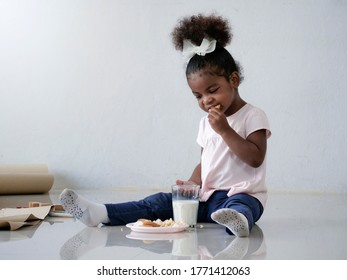 An adorable African girl sit down on the floor and enjoy eating with biskit. Cute littile girl eat a snack in the living room.