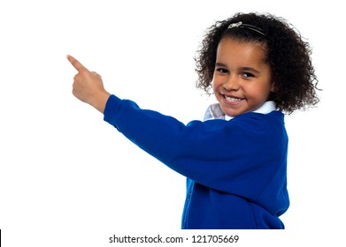 Adorable African kid pointing at copy space area while facing the camera.