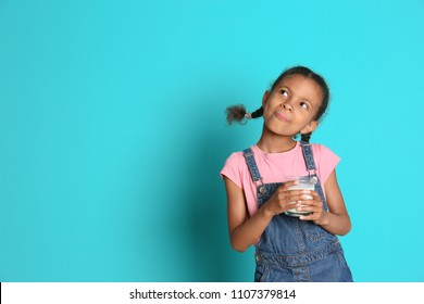 Adorable African-American girl with glass of milk on color background
