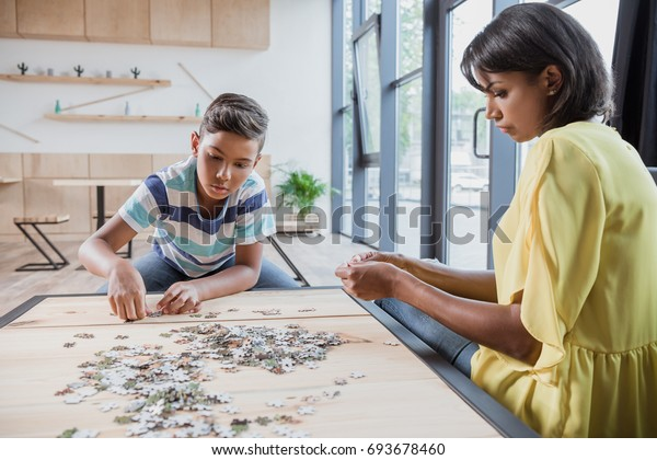 adorable african-american son with mother assembling puzzle