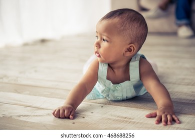 Adorable Afro American baby girl is looking away with interest while crawling on wooden floor at home