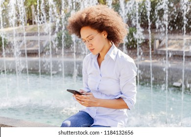 Adorable Afro American Young Woman With Glasses Using Smartphone. Outdoor Portrait Of Mixed Race Female, Casual Wear , Looking At The Phone