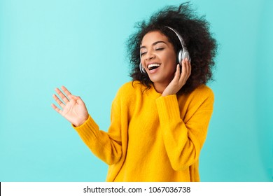 Adorable american woman in yellow shirt singing and having fun while listening to music using wireless earphones isolated over blue background