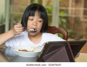 Adorable Asia child girl having lunch while watching movie from tablet. Little Asian child eating dinner and eyes looking cartoon from mobile pc phone.National Eating Disorders Awareness Week.