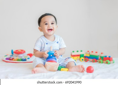 Adorable Asian baby boy 9 months sitting on bed and playing with color developmental toys at home.