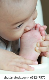 Adorable Asian baby boy sucking his toe, sitting on hi chair.
