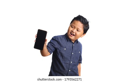 Adorable asian boy in blue is standing while show a blank smartphone screen isolated in white background with copyspace. Selective fokus