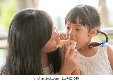 Adorable Asian child eating and sharing butter toast with mom at cafe. Outdoor family lifestyle with natural light.