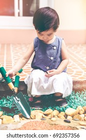 Adorable asian child with gardening equipment. Cute happy girl having fun in the garden at home. Concept about outdoors for children on summer day with bright sunlight. Vintage effect tone.