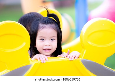 """Adorable Asian child girl  playing """"hide and seek"""" on playground.  Preschool kid peek behind the yellow player machine with friend or her brethren. Happy children sweet smile with playing."""
