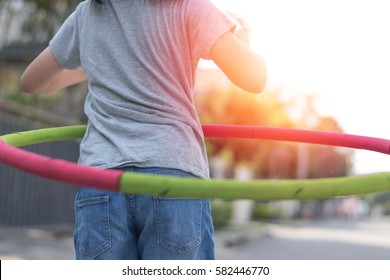 Adorable Asian child girl playing hula hoop in park for exercise in evening. Healthy Asia kid practice  hulahoop racing with light effect.