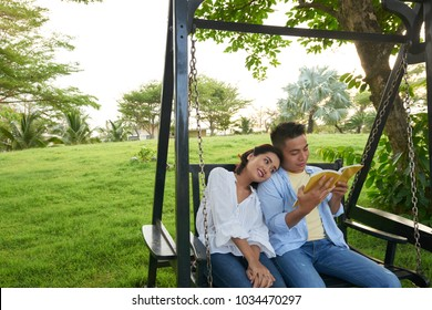 Adorable Asian couple wearing jeans and shirts sitting on porch swing and enjoying each others company, handsome young man wrapped up in reading book, green public park on background