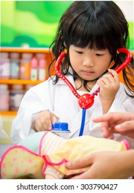 Adorable asian girl role playing doctor occupation wearing white gown uniform