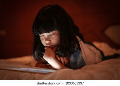 Adorable asian kid reading content and playing tablet while lying on bed, in dim light bedroom background, bright light screen reflex on her face.