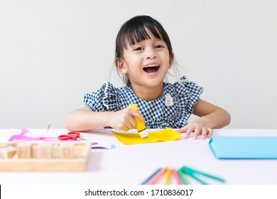 Adorable asian little girl is making do it yourself special gift happy birthday card for her father with happy moment, concept of creativity learning activity for kid development at home.