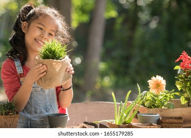 adorable asian little girl is planting spring flowers tree in pots in garden outside house, child education of nature. caring for new life. earth day holiday concept. world environment day. ecology.