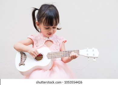 Adorable asian little girl is trying to play ukulele with fully happiness moment, concept of music learning activity for kid development.