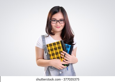 Adorable Asian nerd teenage girl holding some books and pen, on white background