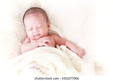 Adorable asian newborn baby in wrap sleeping on white blanket background. Portrait of newborn boy sleep on bed. DAP Action.