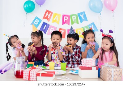 Adorable Asian schoolkids group enjoy the birthday party at home with many gift boxes, happy children boys and girls eating bakery doughnuts  and drink juice together with cheerful in recreation party