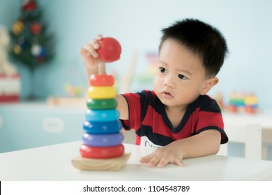 Adorable Asian Toddler baby boy sitting on chair and playing with color developmental toys at home.