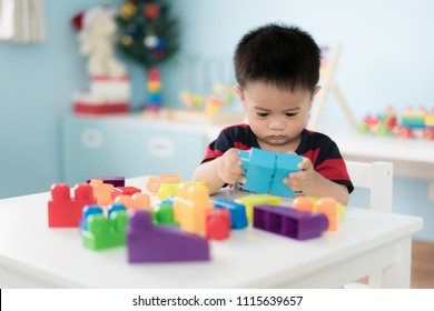 Adorable Asian Toddler baby boy sitting on chair and playing with color block toys at home.
