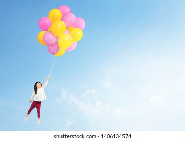 Adorable asian toddler hand holding balloon flying to the sky.