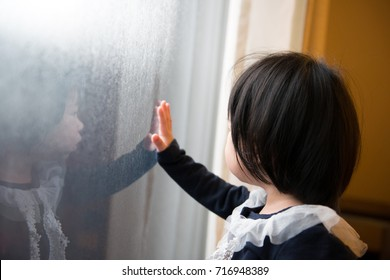Adorable Asian toddler watching the snow through window