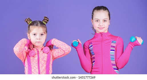 Adorable athletes. Little children developing physical fitness. Small girls enjoy fitness training with weights. Cute sisters doing gym fitness exercises with dumbbells. Sport and fitness for kids.