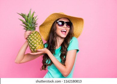 Adorable attractive nice charming curly-haired brunette young smiling girl wearing glasses and sunhat, holding showing pineapple. Isolated over pink pastel background