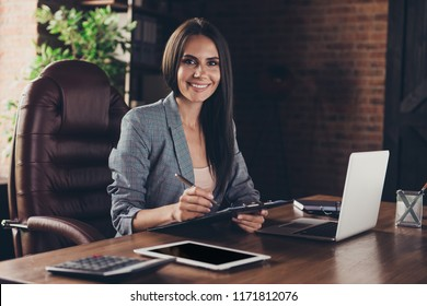 Adorable attractive smart clever young brunette smiling woman wearing checkered jacket, working sitting in office at work place work station