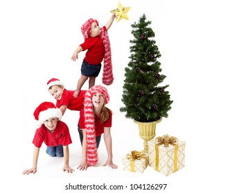 Adorable baby balancing precariously on her siblings backs as she places a star upon the Christmas tree
