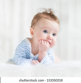 Adorable baby with beautiful blue eyes playing on her tummy in a white nursery