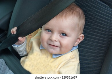 Adorable baby boy with blue eyes sitting in car, summer.