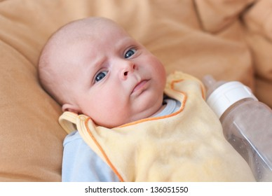 Adorable baby boy with blue eyes three months old with big milk bottle