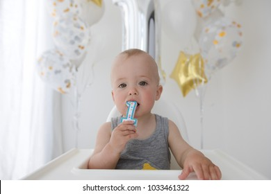 Adorable baby boy celebrating first birthday . Kids birthday party decorated with balloons Child eating cake and candy.