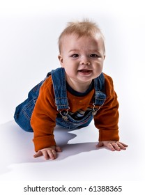 Adorable baby boy crawling toward the viewer wearing an orange shirt and overalls