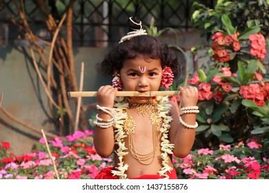 Adorable baby boy dressed up as little Krishna and playing with wooden flute in garden on the occasion of Krishna janmastami