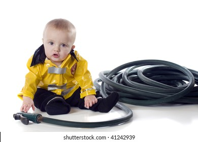 An adorable baby boy in a fireman's suit, reaching for a hose.  Isolated on white.