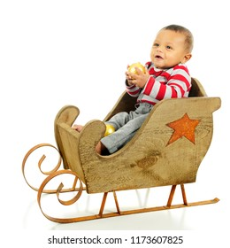 An adorable baby boy happily sitting in a rustic sleigh holding a gold Christmas ornament.  On a white background.