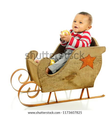 b8b548988e35 An adorable baby boy happily sitting in a rustic sleigh holding a gold  Christmas ornament.