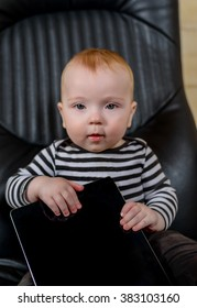 Adorable Baby Boy Holding his Tablet Computer While Sitting on an Office Chair and Looking at the Camera.
